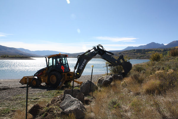 Workers move boulders into place at Green Mountain Reservoir to prevent unauthorized boat launches.