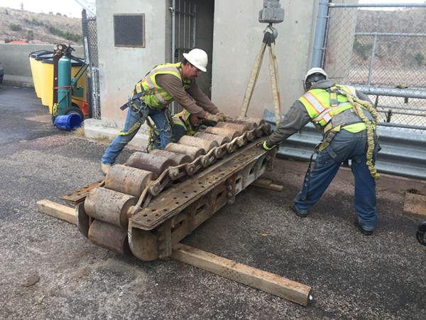 (Left) Workers inspecting roller train after removal.