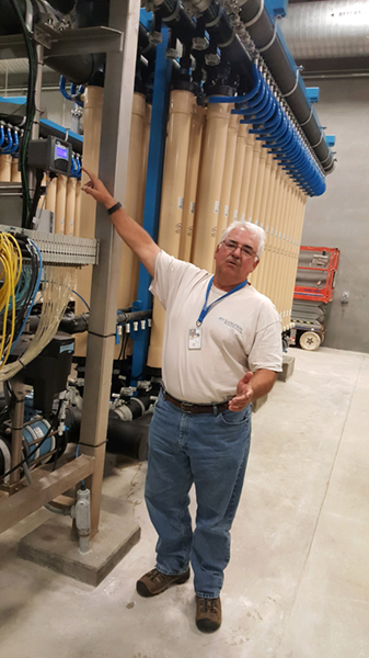 Tom Thompson inside the Standing Rock Rural Water Supply System water treatment plant explains the advanced water filtration system.