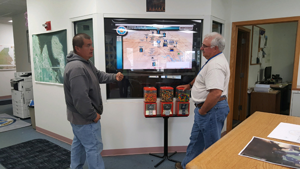 Tom Ridley (left) and Tom Thompson (right) discuss the computer program that monitors the newly operational Standing Rock Rural Water Supply System. This interactive computer program provides real-time information on each of the System components.
