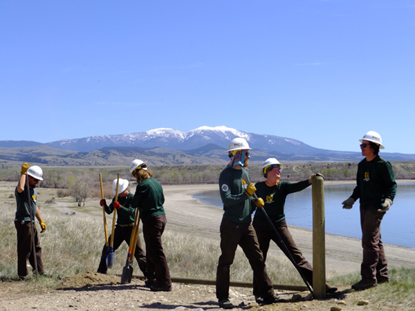 A Montana Conservation Corps crew replaces deteriorated fence to block unauthorized OHV access.