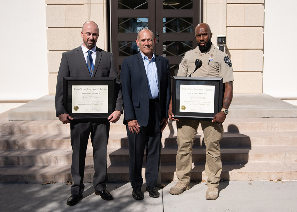 Pictured are security officers Kevin Paulsen (left) and Byron Sandifer (right) who were recognized by Regional Director Terry Fulp (center) for saving a man's life.