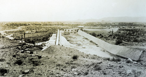 The purpose of the forebay was to hold a steady head of water for power generation.  More importantly, it allowed the water to settle and drop its silt and sand to the bottom of the forebay where could be flushed out as necessary, 1914. (Reclamation photograph)