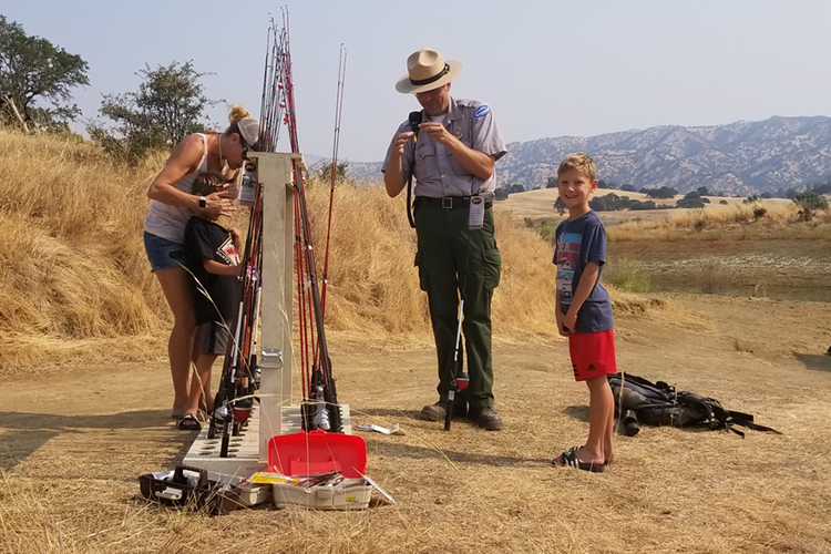 Park ranger helps to tie a line with guests at the free fishing event.