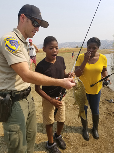Game warden holds fish that child caught.