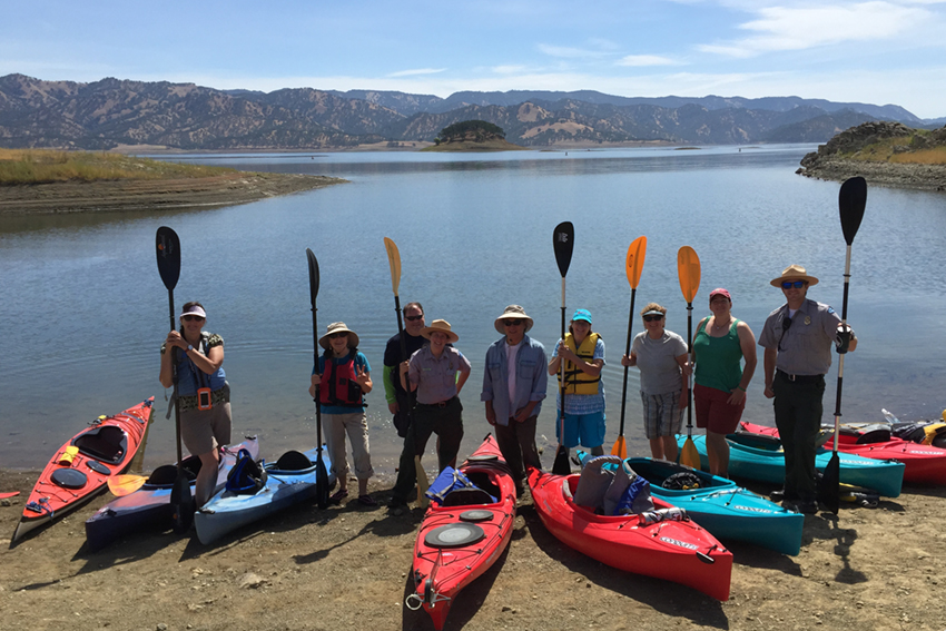 Visitors pose with kayaks before event.