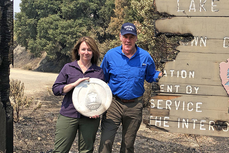Photo of Reclamation Commissioner Brenda Burman holds a fire-salvaged Reclamation seal, here with Interior Secretary Ryan Zinke, at Whiskeytown Lake on Aug. 12, 2018.