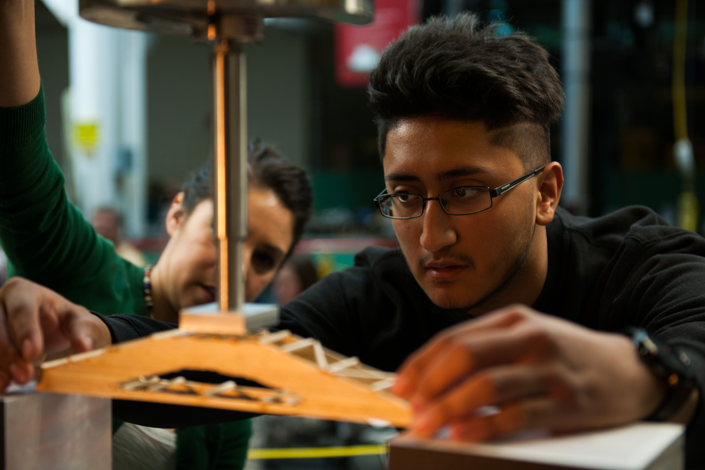 A student sets his bridge before increased loads of weight are applied to measure the bridge's efficiency number.