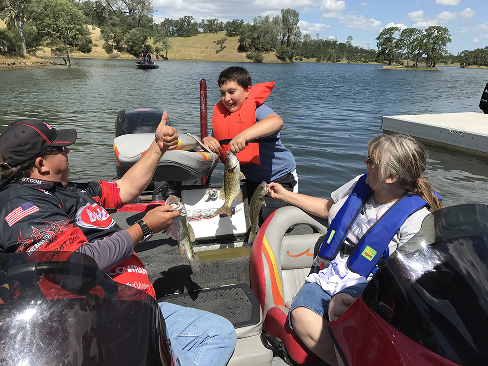A happy C.A.S.T. for Kids participant holds up one of five fish he caught on Lake Berryessa.