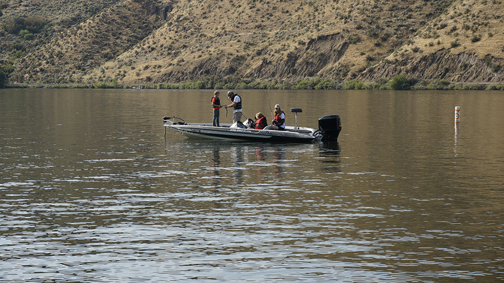 Boat captain helping participant with his catch of the day at the Black Canyon C.A.S.T. event in Emmett, Idaho, August 19, 2017.