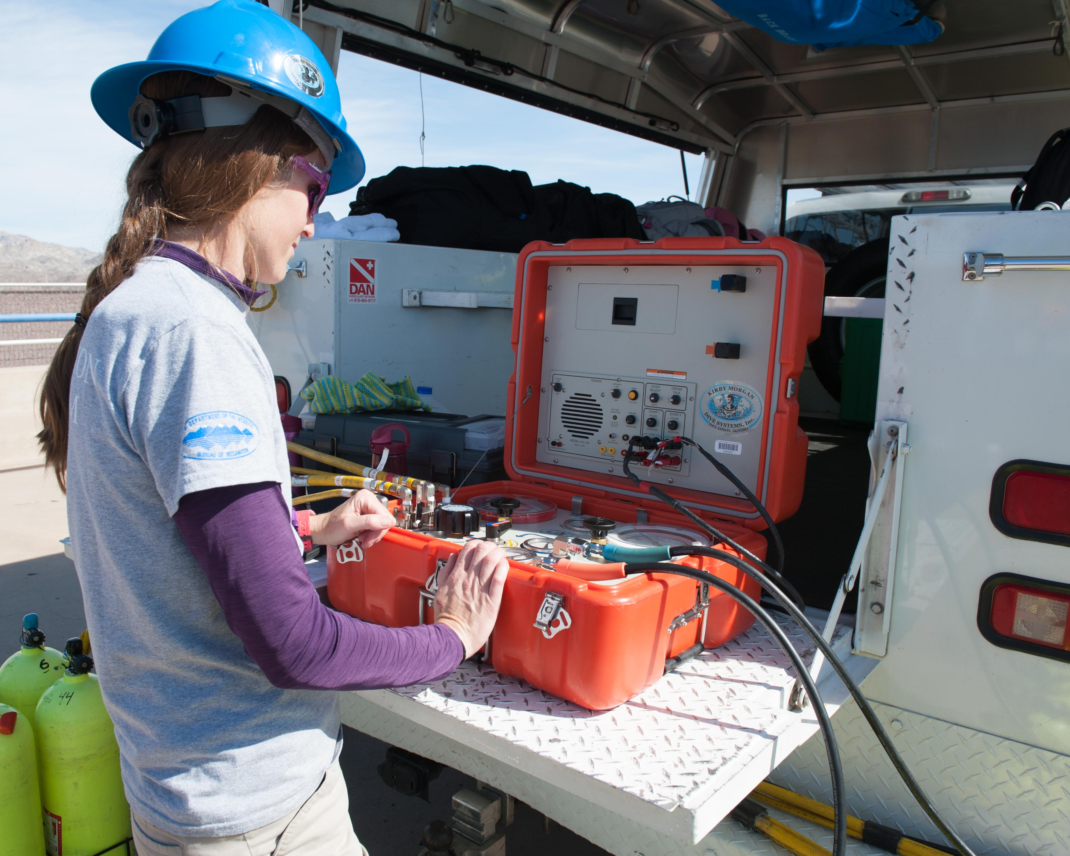Dive Team Leader, Caireen Ulepic operates communication box for Surface-Supplied Air Dive