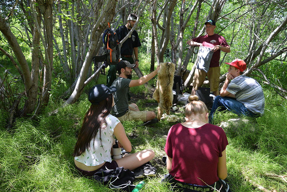 Students looking at and learning about an animal pelt.