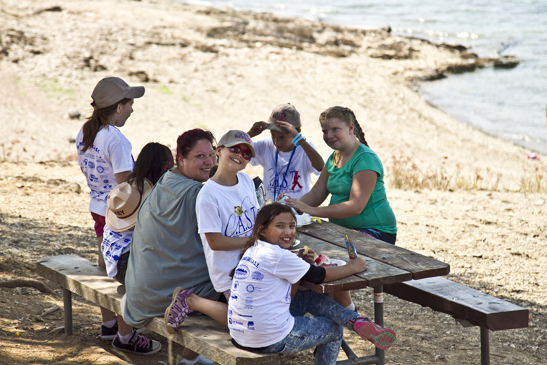 A group of participants pose for a picture during the barbecue lunch at the C.A.S.T. for Kids event at New Melones Lake