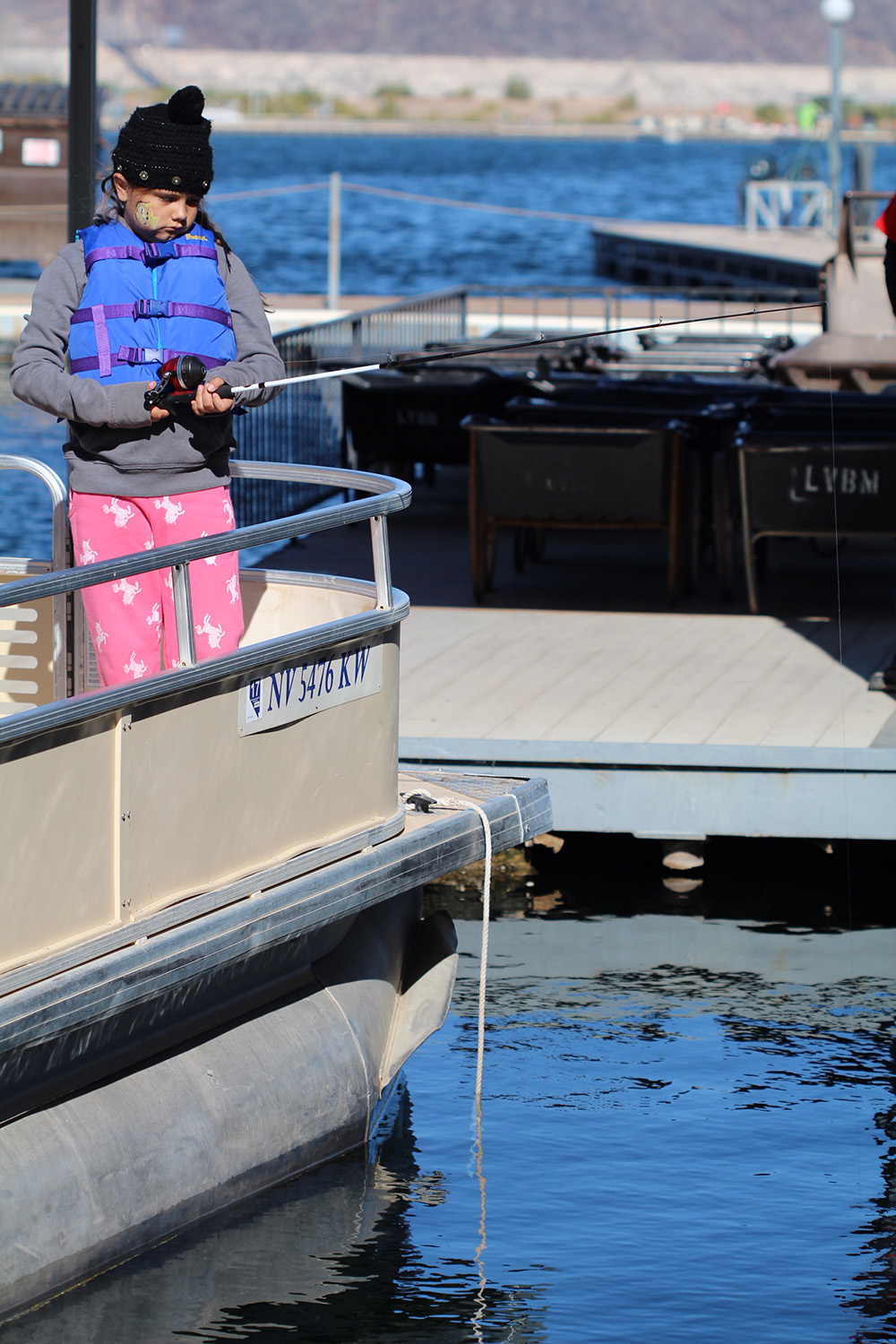 A girl fishing from a boat at the C.A.S.T. for Kids event at Lake Mead.