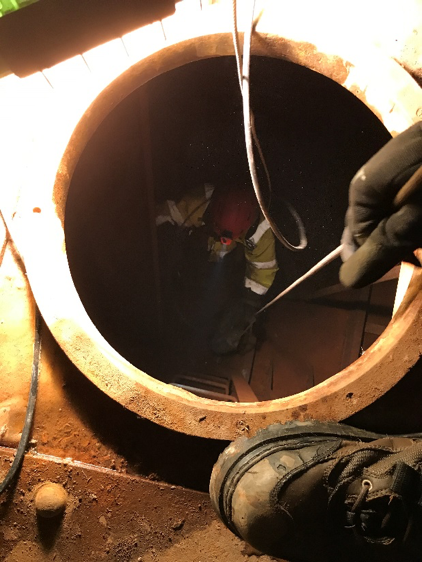 Anodes were lowered by rope into a pontoon of the Yankee Fork Gold Dredge during the cathodic protection system installation, Sept 24-28, 2017. Fall protection system is attached to Henderson inside the pontoon and a rope is attached to the anode, to ensure the safe lowering of the 44-pound anode.