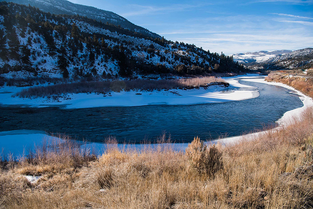 The Colorado River as it flows through Grand County, Colorado, during winter with snow and ice around the banks.
