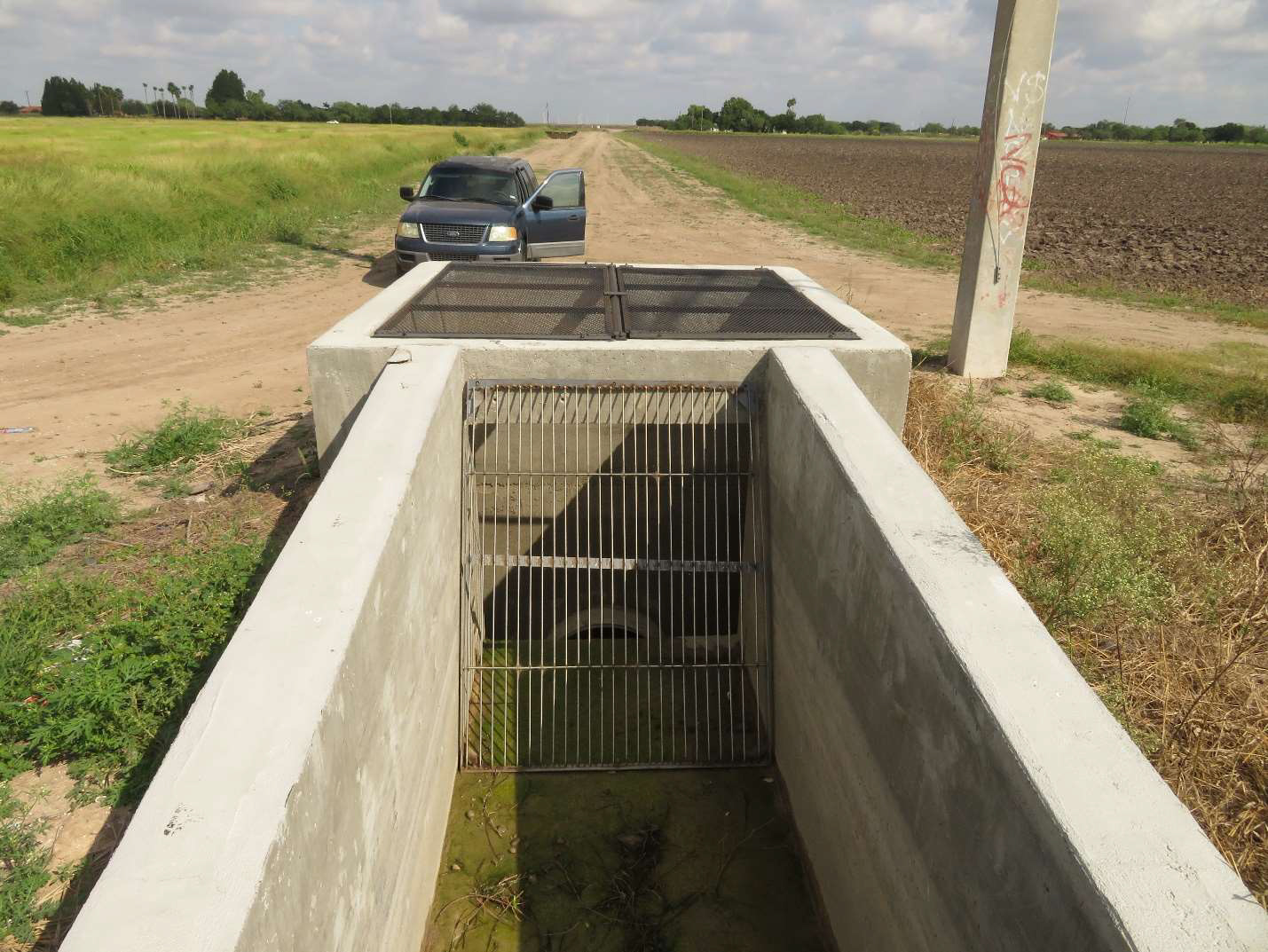 A canal structure and pipe with a grating on it. It is located in agricultural field.