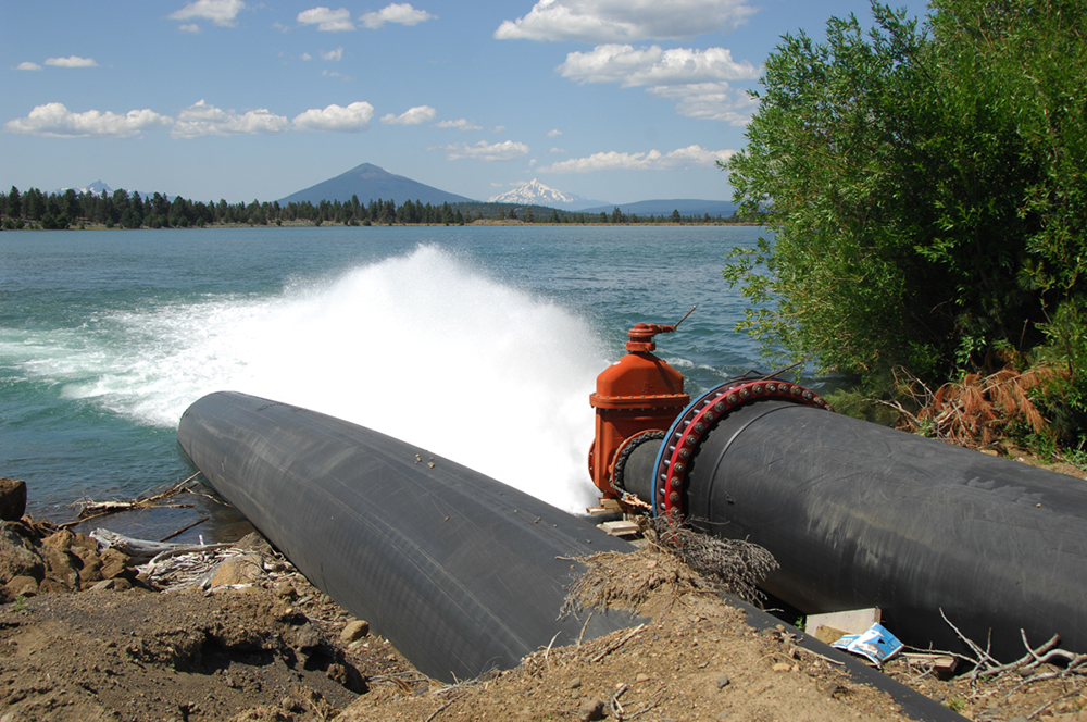 Photo of two pipes with one releasing water to a lake. A volcano cone in the distance.