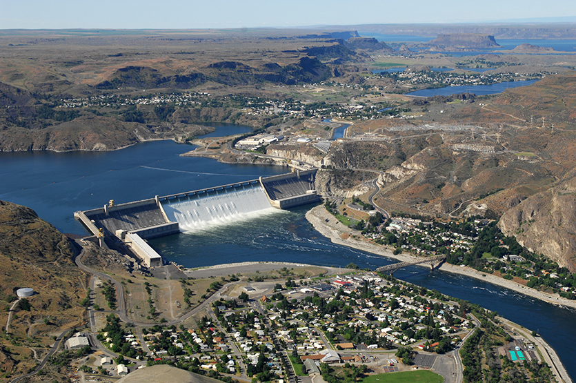 Aerial view of Grand Coulee Dam releasing downstream an unusually large and late spring time water flows of over 200,000 cfs. Broken out, it's  33,800 cfs, over the spillway and 167,000 cfs through the hydropower generators.