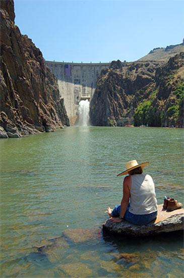Lady sitting in water looking at Owyhee Dam in Oregon.