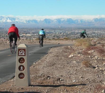 Three cyclist riding past a mile marker on the River Mountains Loop Bike Trail, located within the Robert B Griffith Water Project in Henderson Nevada.
